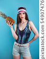 Fashion summer portrait beautiful woman in sun pink visor and pineapple over blue background 54907476