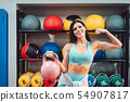 Young adult girl doing strength exercises in the gym 54907817