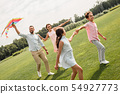 Having fun together. Happy and young family of four launcinging a kite in the field. 54927773