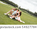 Having fun together. Happy family sitting on the grass in the park and blowing soap bubbles with 54927784