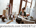 Young woman tailor in design studio looking to the window 54928712