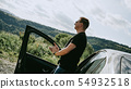 Back view of a man standing on a mountain view. Traveler is enjoying landscape 54932518