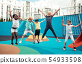 Cheerful pupils jumping up and down on a sports ground. 54933598