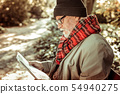 Handsome aged man reading a newspaper in the park. 54940275