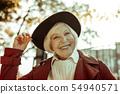 Happy elderly woman taking a walk in a park. 54940571