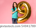 Cute girl with number 9 balloon at studio background 54941789