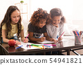 Schoolgirls drawing with colorful pencils at home 54941821