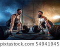 Two muscular bearded tattoed athletes training at gym 54941945