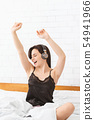 Energetic girl dancing in bed, listening to music 54941966
