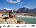 Hiker sitting on river shore, looking the 54969199