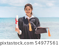 Graduated woman in cap and gown hold certificated 54977561