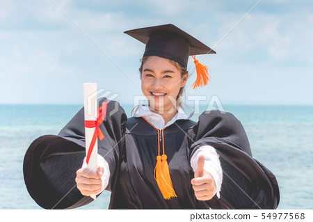 Graduated woman in cap and gown hold certificated 54977568