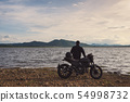 Young biker standing on side of big bike with 54998732