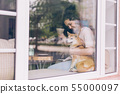 Beautiful young woman drinking tea in cafe hugging cute dog on window sill 55000097