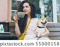 Attractive girl drinking tea outdoors in cafe patting dog sitting in cafe 55000158