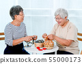 Two Asian elderly woman sit on chair and have 55000173