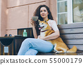 Beautiful woman relaxing outdoors in cafe with pet dog and cup of coffee 55000179