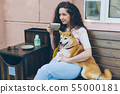 Young lady drinking tea hugging shiba inu dog outdoors in cafe sitting on bench 55000181
