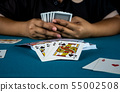 The gambler is playing cards in his hand. 55002508