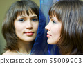 Happy young woman looking in the mirror 55009903