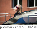 Happy young woman with a car 55010238