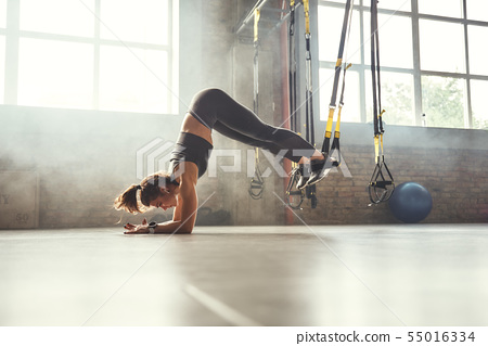 Making perfect body. Young athletic woman exercising with suspension straps in the gym