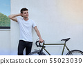 Handsome hipster man posing with bicycle in the city. 55023039