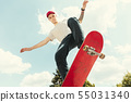 Skateboarder doing a trick at the city's street in sunny day 55031340