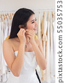 Beautiful bride in white wedding dress puts on earring. 55035753