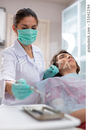 Serious middle-aged female doctor taking a dental mirror 55042294