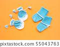 Baby gloves and socks on orange background. 55043763