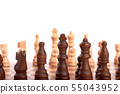 Row of white and black wooden chess pieces on a 55043952