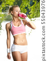 Thirsty sporty woman drinking water after training 55043976