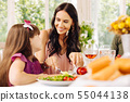 Dark-haired mommy taking care of her girl while having lunch 55044138