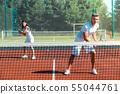 Couple feeling joyful while training on court playing tennis 55044761