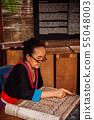 Laotian Senior woman do Batik fabric painting 55048003
