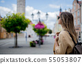 Woman in sunglasses and backpack in aged city center square. Poland 55053807