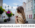 Woman in sunglasses and backpack in aged city center square. Poland 55053808