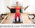 Woman doing pilates arm work with straps 55060978