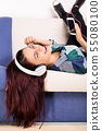 Young girl relaxing while listening to music 55080100
