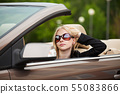 Young woman driving a convertible car 55083866
