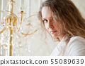 Beautiful woman against a chandelier 55089639