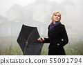 Young woman in autumn foggy morning 55091794