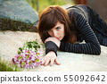 Sad young woman lying on the tombstone 55092642