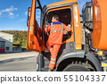 Garbage removal worker getting into the disposal vehicle 55104337