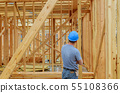 A construction day laborer carrying wood beams. 55108366