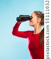 Woman looking through binoculars 55111632