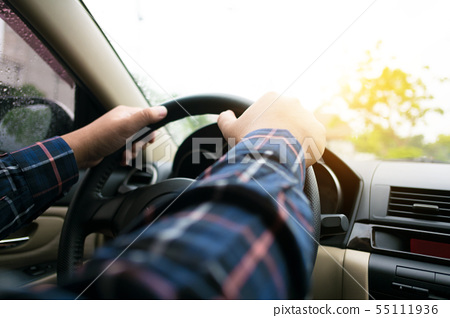 close up of hands of man driving a car 55111936