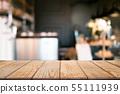 empty wooden desk over blurred coffee shop 55111939