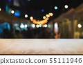 empty wood table in front of blurred montage night 55111946